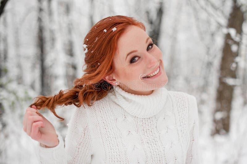 Menina bonita do gengibre na camiseta branca na neve dezembro da floresta do inverno no parque Retrato Tempo bonito do Natal imagem de stock royalty free