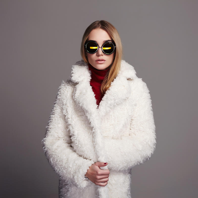 Menina bonita do inverno na pele e nos óculos de sol brancos Fôrma do inverno Mulher nova 15 fotos de stock royalty free