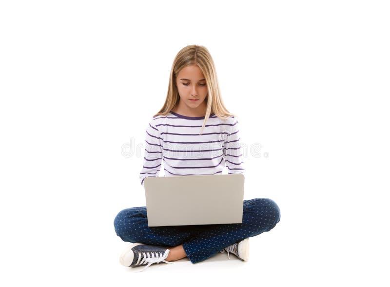 Menina bonita do jovem adolescente que senta-se no assoalho com pés cruzados e que usa o portátil, fotografia de stock