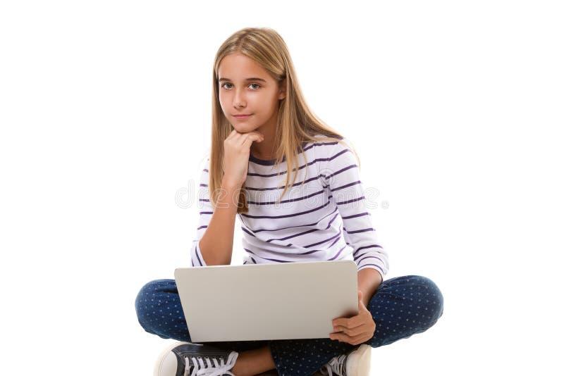 Menina bonita do jovem adolescente que senta-se no assoalho com pés cruzados e que usa o portátil, isolado fotos de stock