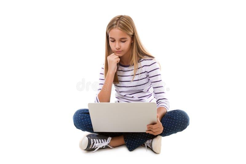 Menina bonita do jovem adolescente que senta-se no assoalho com pés cruzados e que usa o portátil, isolado foto de stock royalty free