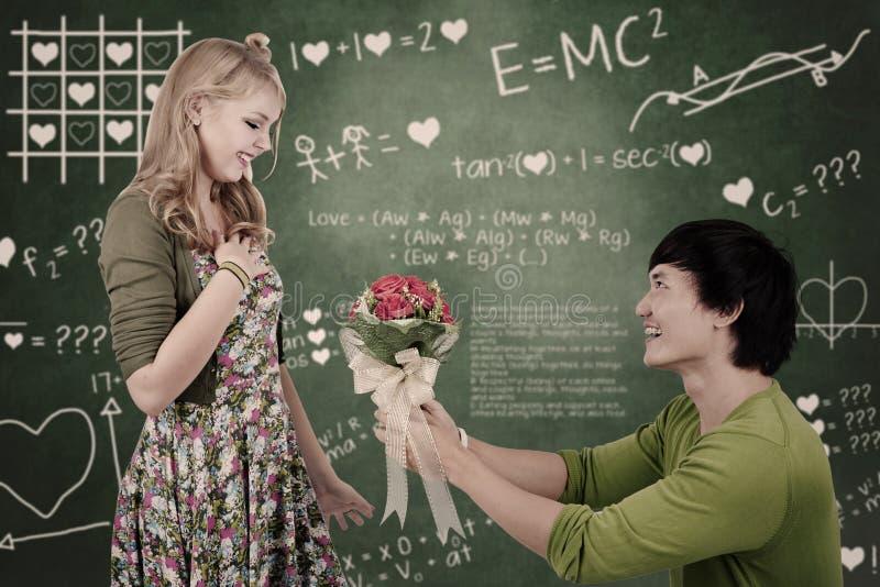 A menina bonita do lerdo obtem flores na classe foto de stock royalty free