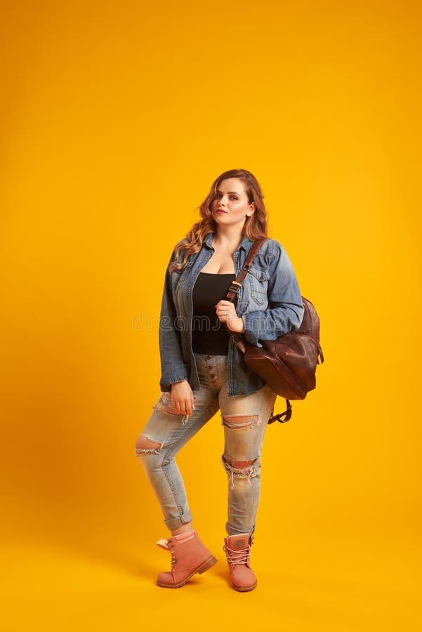 Menina bonita do mais-tamanho na roupa ocasional com a trouxa no shoulde fotografia de stock
