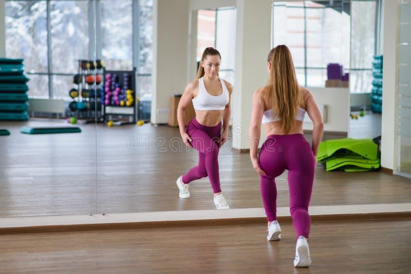 Menina bonita do modelo da aptidão com corpo perfeito e a forma que levantam no gym perto do espelho Estilo de vida desportivo e  fotos de stock