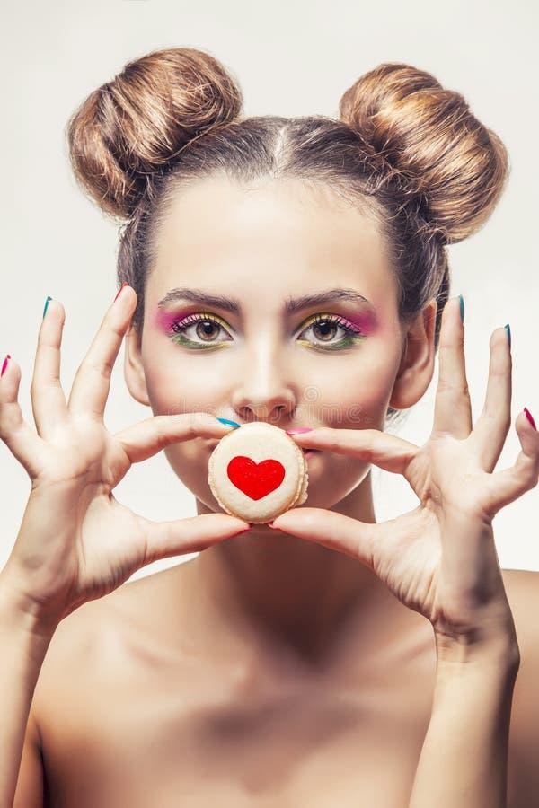 Menina bonita do modelo de forma com as cookies doces com corações na imagens de stock