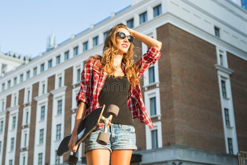 Menina bonita do moderno com os óculos de sol vestindo da placa do patim imagens de stock royalty free