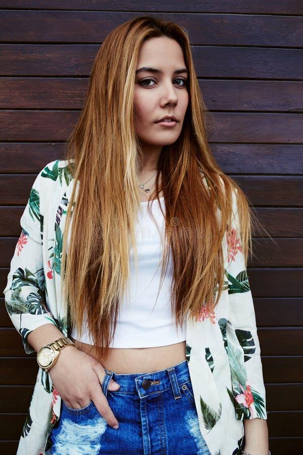 menina bonita do moderno que veste a roupa na moda que está no fundo de madeira da parede imagens de stock