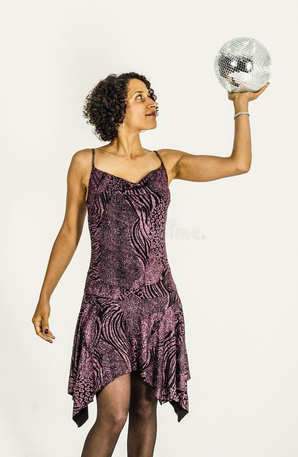 Menina bonita do mulato em um vestido brilhante com bola do disco fotografia de stock royalty free