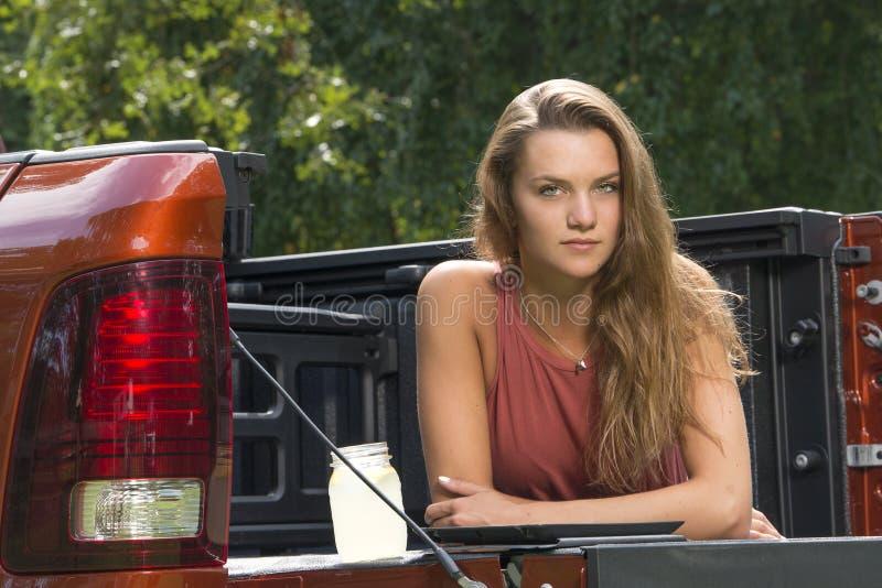 A menina bonita do país suporta sobre do caminhão de recolhimento foto de stock