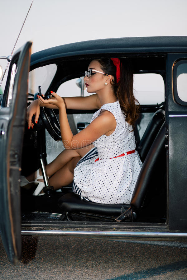 Menina bonita do pino-acima dentro do carro do vintage fotografia de stock