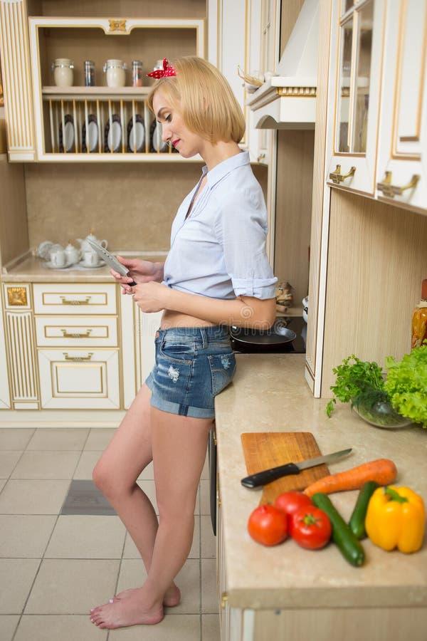 Menina bonita do pino-acima em uma cozinha que guarda uma faca fotos de stock
