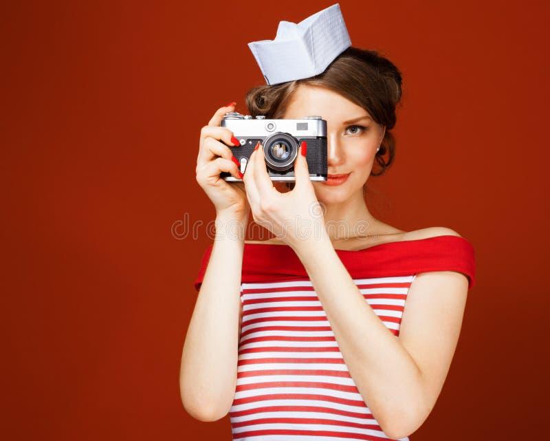 A menina bonita do pino-acima que guarda uma câmera do vintage e dirige-a em linha reta à câmera Fundo vermelho, fim acima imagens de stock royalty free