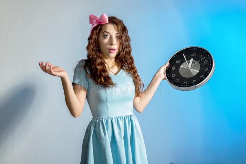 Menina bonita do pinup em um vestido azul que guarda o pulso de disparo grande em um fundo azul fotografia de stock royalty free