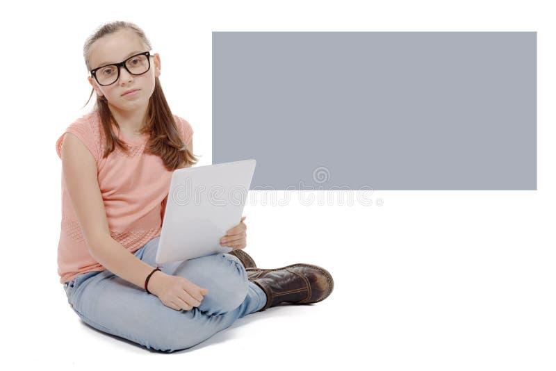 Menina bonita do preteen com um tablet pc fotografia de stock royalty free