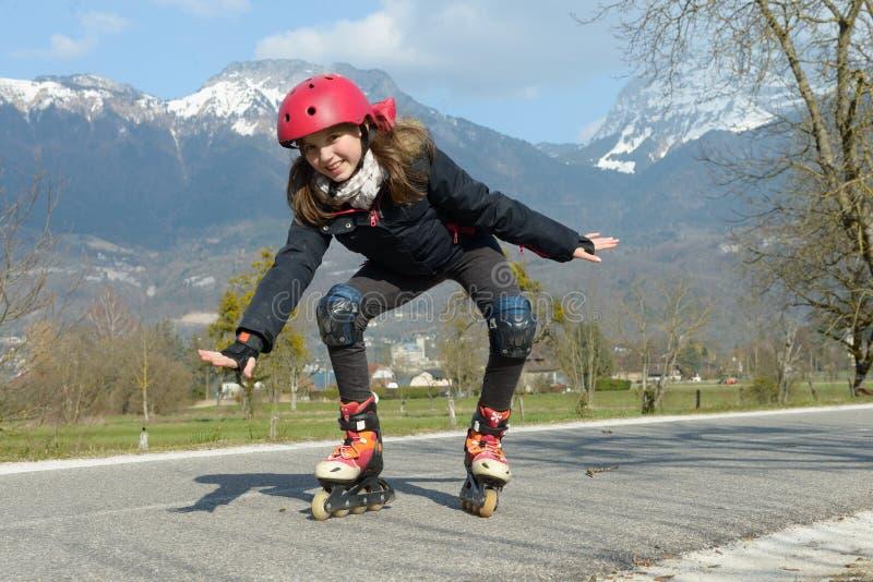 Menina bonita do preteen em patins de rolo no capacete em uma trilha imagem de stock royalty free