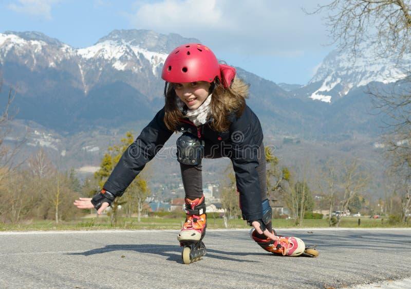 Menina bonita do preteen em patins de rolo no capacete em uma trilha fotografia de stock