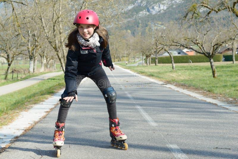 Menina bonita do preteen em patins de rolo no capacete em uma trilha imagem de stock