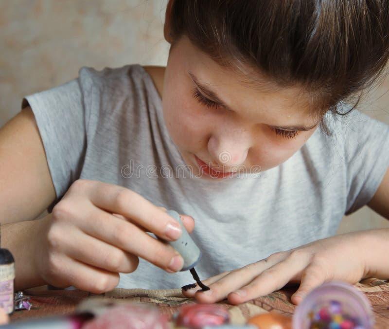 A menina bonita do preteen faz o tratamento de mãos fotografia de stock