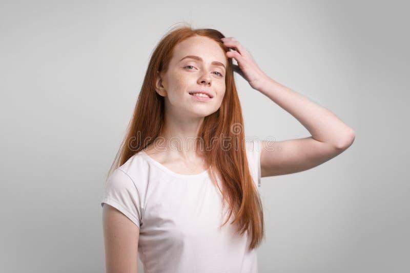 Menina bonita do ruivo com sardas que sorri olhando a câmera fotos de stock royalty free