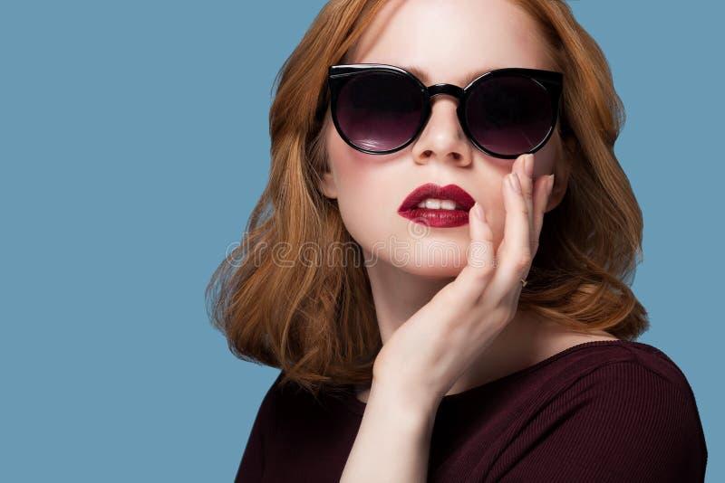 Menina bonita do ruivo em uma composição brilhante do batom vermelho marrom da blusa em óculos de sol pretos em um fundo azul imagem de stock