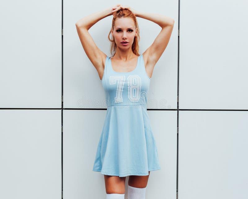 A menina bonita do ruivo levanta na câmera, no fundo cinzento da parede Pele macia, vestido azul do verão foto de stock royalty free