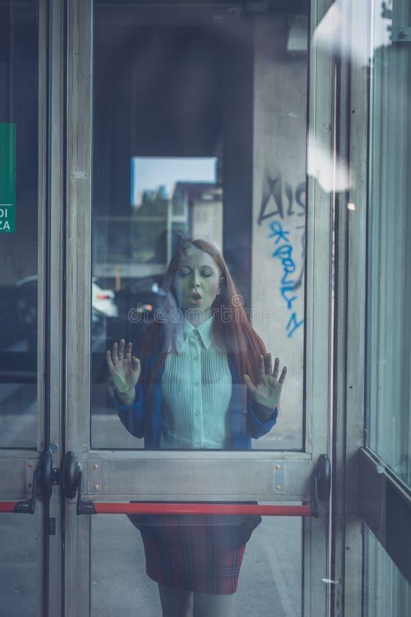 Menina bonita do ruivo que levanta atrás de uma porta de vidro fotos de stock