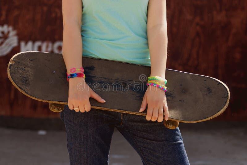 Menina bonita do skater que guarda o skate fotografia de stock royalty free