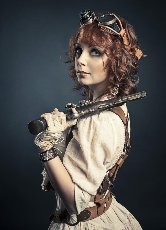 Menina bonita do steampunk do redhair com arma fotografia de stock