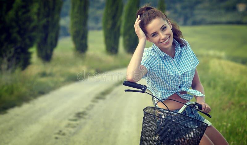 Menina bonita do vintage que senta-se ao lado da bicicleta, horas de verão foto de stock royalty free