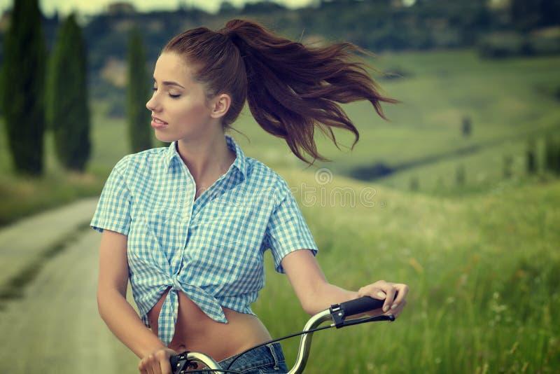 Menina bonita do vintage que senta-se ao lado da bicicleta, horas de verão fotografia de stock royalty free