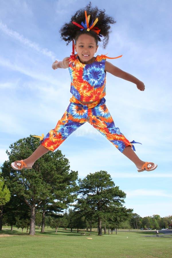 Menina bonita dos anos de idade seis que salta no parque imagens de stock royalty free