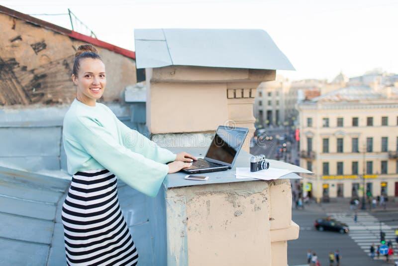 A menina bonita e à moda trabalha para um portátil no telhado da casa na cidade velha na tabela são igualmente os originais e o C fotografia de stock