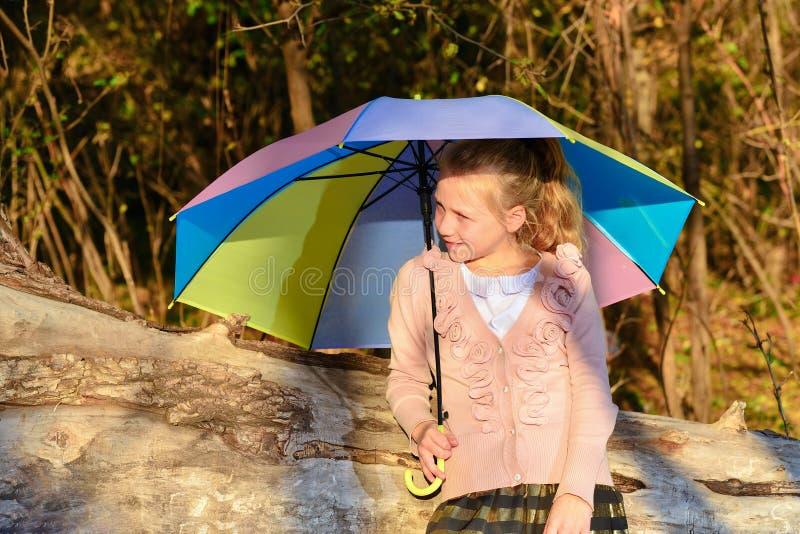 Menina bonita e bonito com um guarda-chuva da cor na queda no parque, retrato de uma menina sob o sol da noite do outono foto de stock royalty free