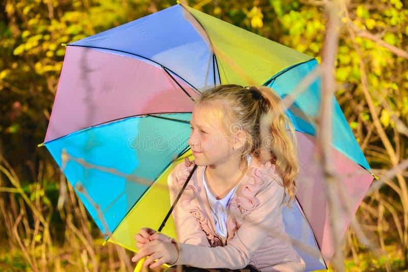 Menina bonita e bonito com um guarda-chuva da cor na queda no parque, retrato de uma menina sob o sol da noite do outono fotos de stock royalty free