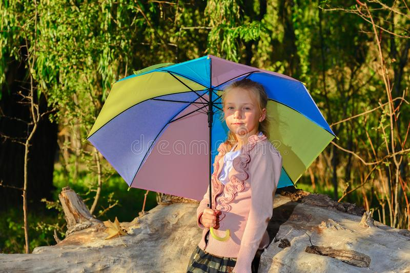 Menina bonita e bonito com um guarda-chuva da cor na queda no parque, retrato de uma menina sob o sol da noite do outono imagens de stock