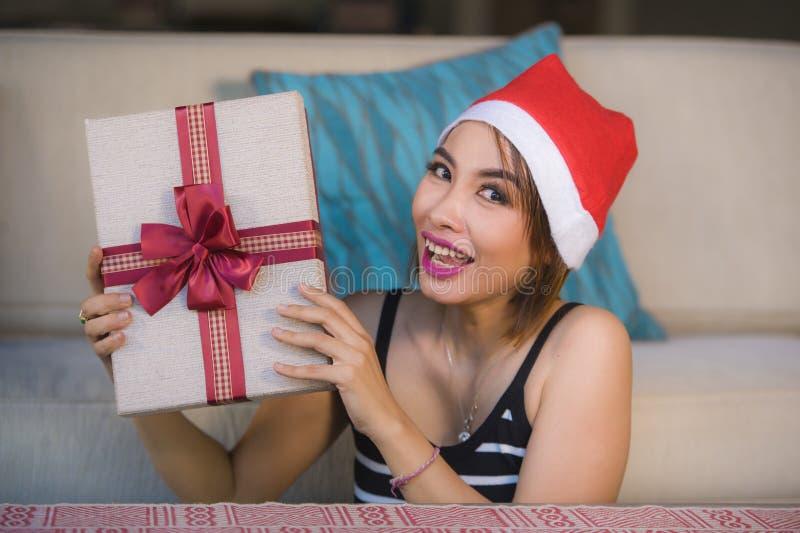 Menina bonita e feliz nova no chapéu de Santa que guarda a caixa do presente de Natal com fita que sorri em casa sofá alegre e ex foto de stock royalty free