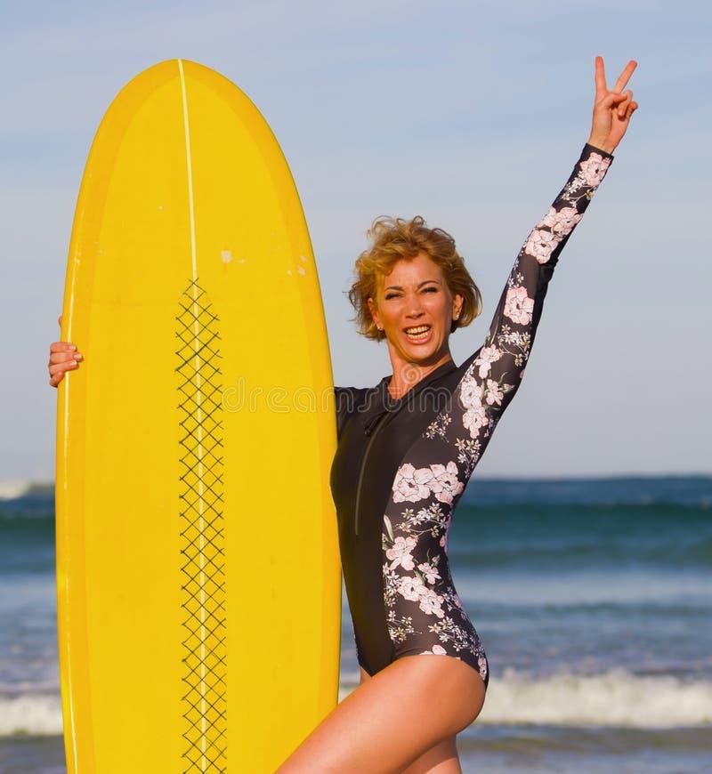 Menina bonita e feliz 'sexy' nova do surfista que guarda férias de verão de apreciação alegres de sorriso amarelas da placa de re fotos de stock