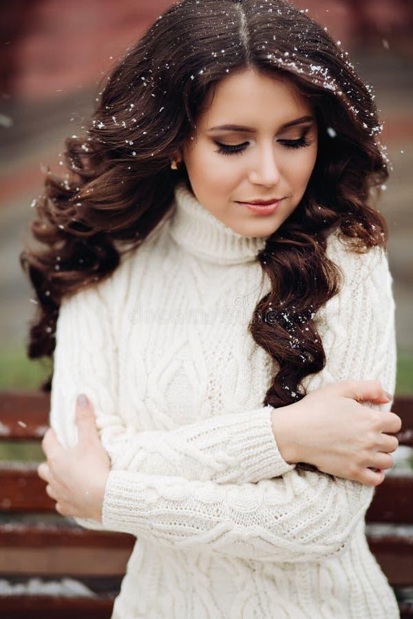A menina bonita e muito à moda nova com cabelo escuro longo levanta em um vestido branco por muito tempo feito malha Retrato da f imagens de stock