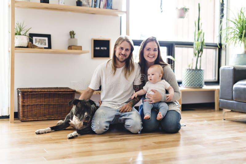 Menina bonita e seu pai que obtêm algum amor de cachorrinho na sala de visitas fotos de stock royalty free