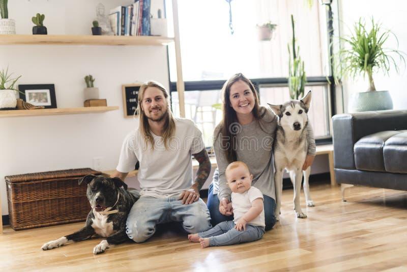 Menina bonita e seu pai que obtêm algum amor de cachorrinho na sala de visitas imagem de stock royalty free