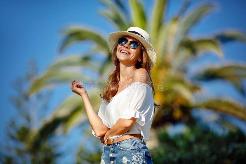 A menina bonita e 'sexy' bronzeada em um chapéu branco e em vidros sorri imagem de stock royalty free
