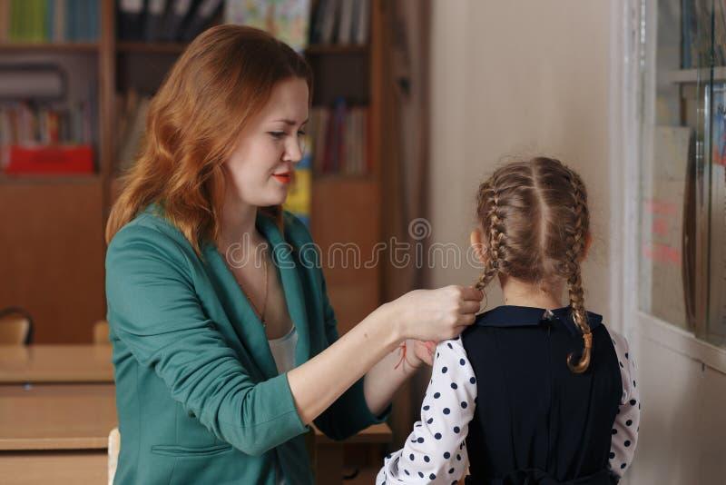 Menina bonita e sua mãe nova que leem um livro junto ou que estudam em casa fotografia de stock
