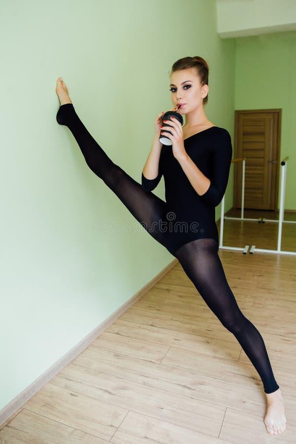 A menina bonita elegante do dançarino de bailado moderno com corpo perfeito senta-se no assoalho no salão do estúdio fotos de stock royalty free