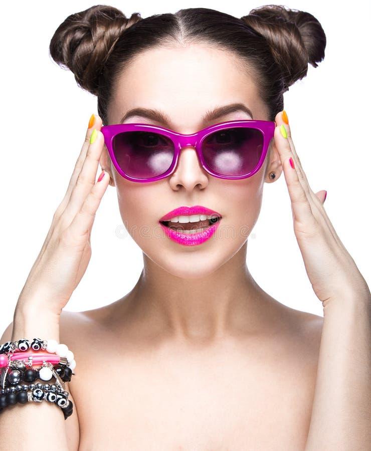 Menina bonita em óculos de sol cor-de-rosa com composição brilhante e os pregos coloridos Face da beleza fotos de stock