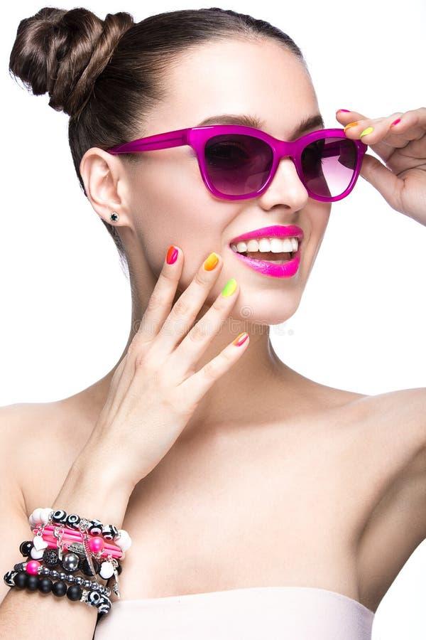 Menina bonita em óculos de sol cor-de-rosa com composição brilhante e os pregos coloridos Face da beleza imagens de stock