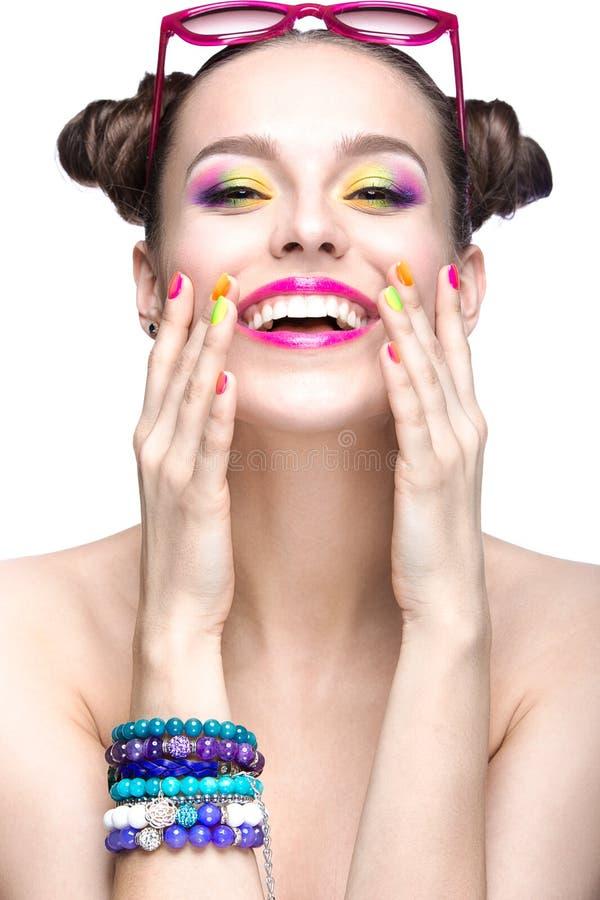 Menina bonita em óculos de sol cor-de-rosa com composição brilhante e os pregos coloridos Face da beleza imagem de stock royalty free