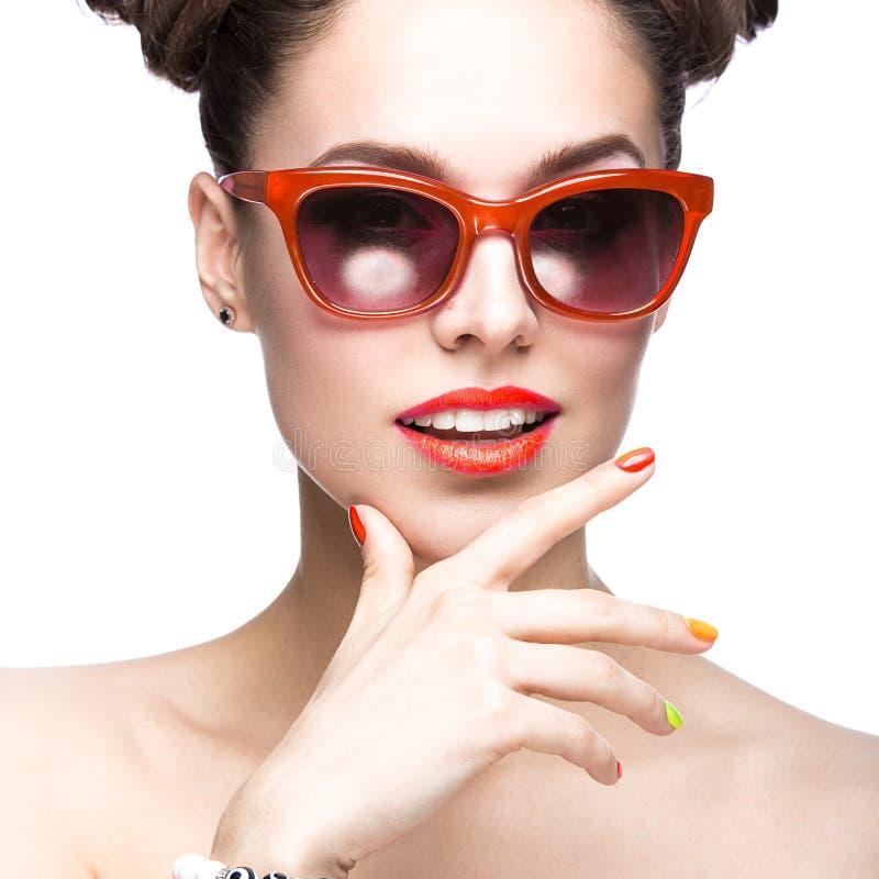 Menina bonita em óculos de sol vermelhos com composição brilhante e os pregos coloridos Face da beleza imagens de stock