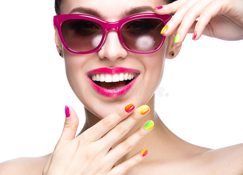 Menina bonita em óculos de sol vermelhos com composição brilhante e os pregos coloridos Face da beleza fotografia de stock royalty free