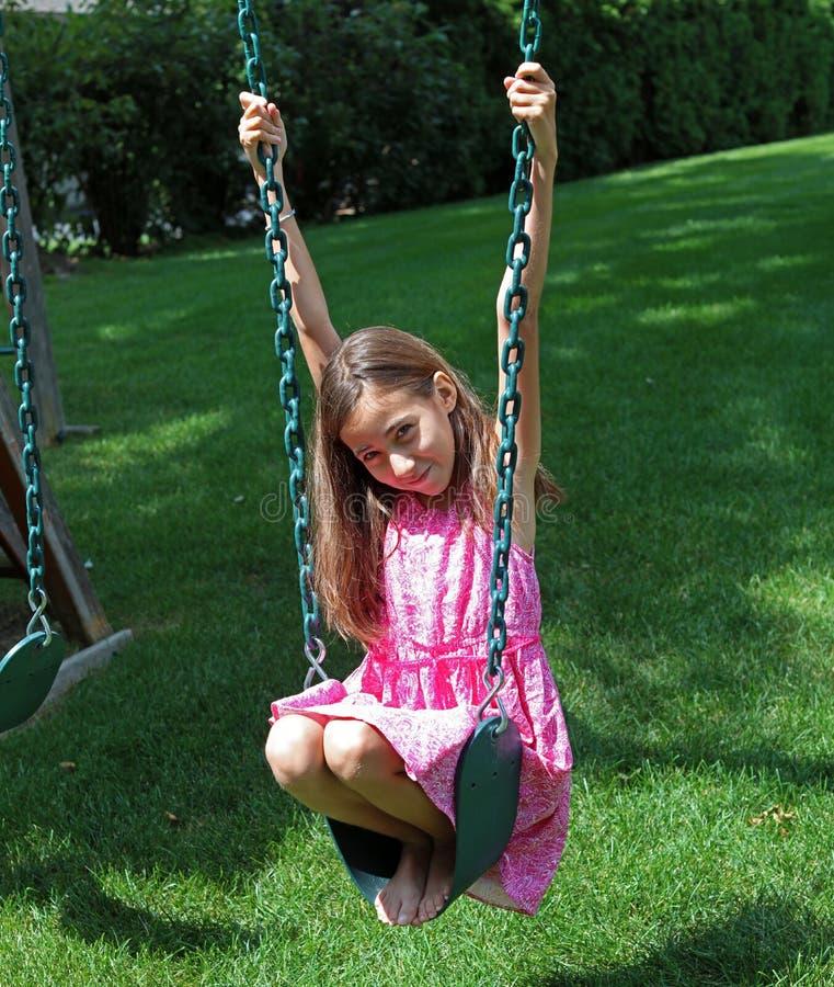 Menina bonita em balanços no parque com o vestido cor-de-rosa durante o verão em Michigan fotografia de stock royalty free