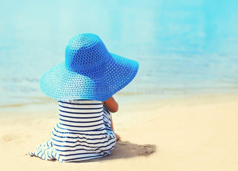 Menina bonita em chapéu listrado do vestido e de palha que aprecia o mar imagem de stock